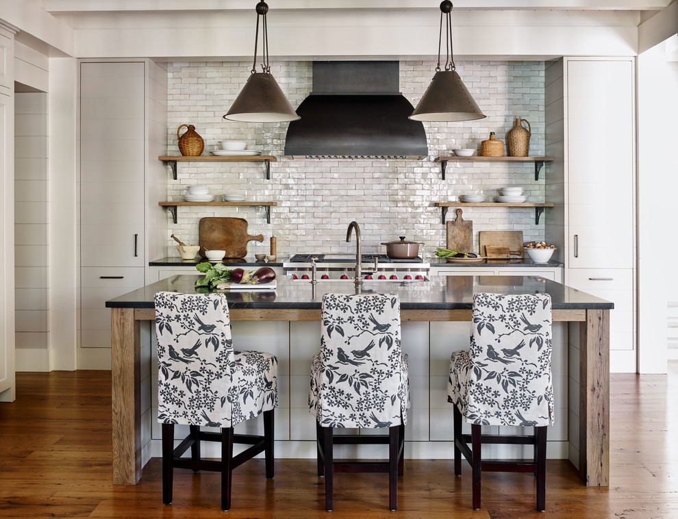 Example of a mountain style galley medium tone wood floor and brown floor kitchen design with a farmhouse sink, flat-panel cabinets, gray cabinets, white backsplash, subway tile backsplash, stainless steel appliances, an island and black countertops