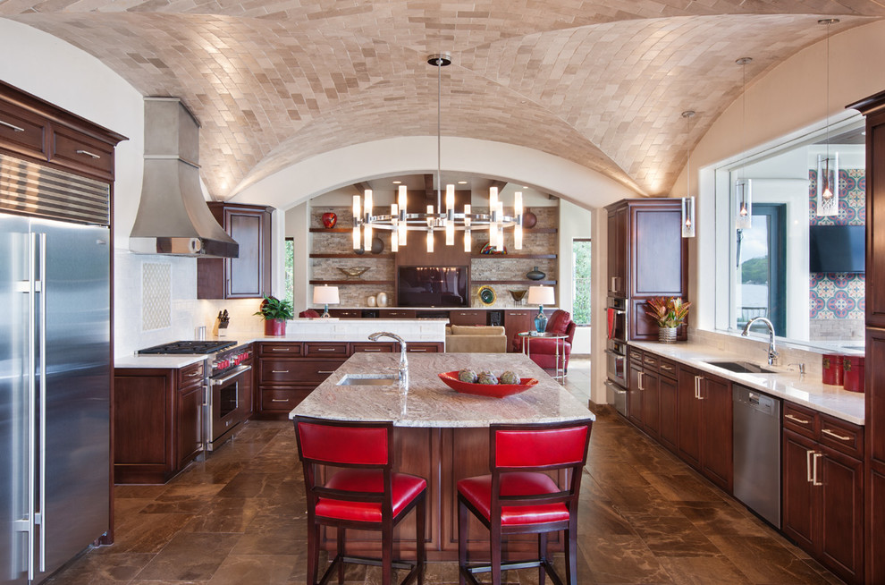 Kitchen - mediterranean u-shaped kitchen idea in Austin with an undermount sink, raised-panel cabinets, dark wood cabinets, beige backsplash and stainless steel appliances