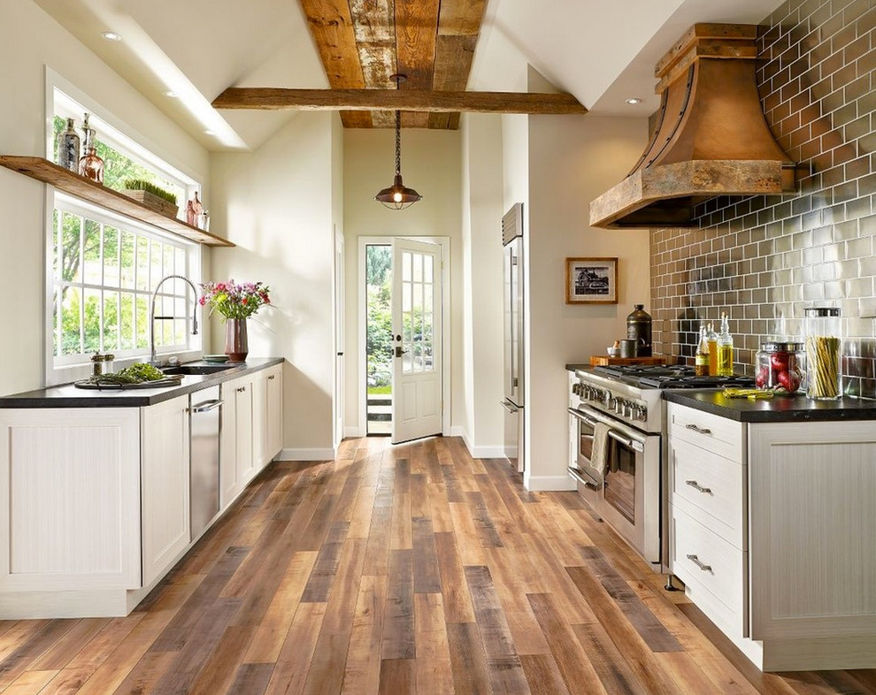 Example of a farmhouse medium tone wood floor and brown floor kitchen design in San Francisco with shaker cabinets, light wood cabinets, black backsplash, subway tile backsplash, stainless steel appliances and no island