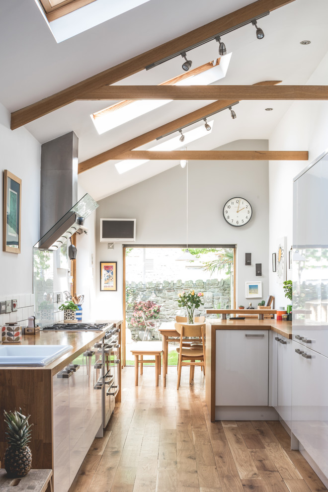 Mid-sized farmhouse u-shaped medium tone wood floor and brown floor open concept kitchen photo in Other with flat-panel cabinets, white cabinets, wood countertops, white backsplash, paneled appliances, a peninsula, brown countertops and a drop-in sink