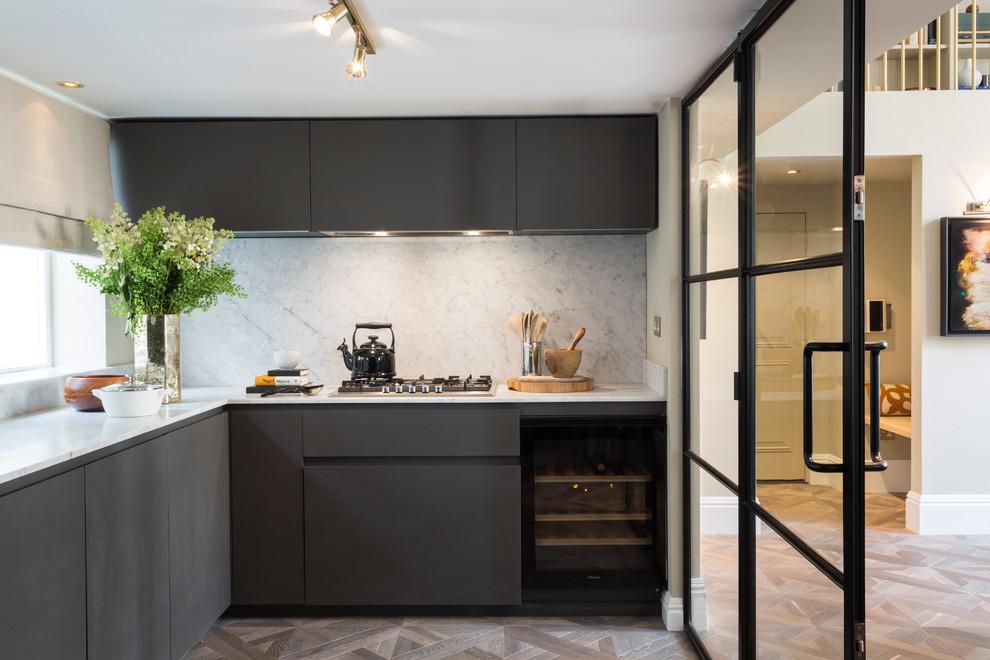 Small trendy l-shaped light wood floor enclosed kitchen photo in London with flat-panel cabinets, black cabinets, gray backsplash, stone slab backsplash and no island