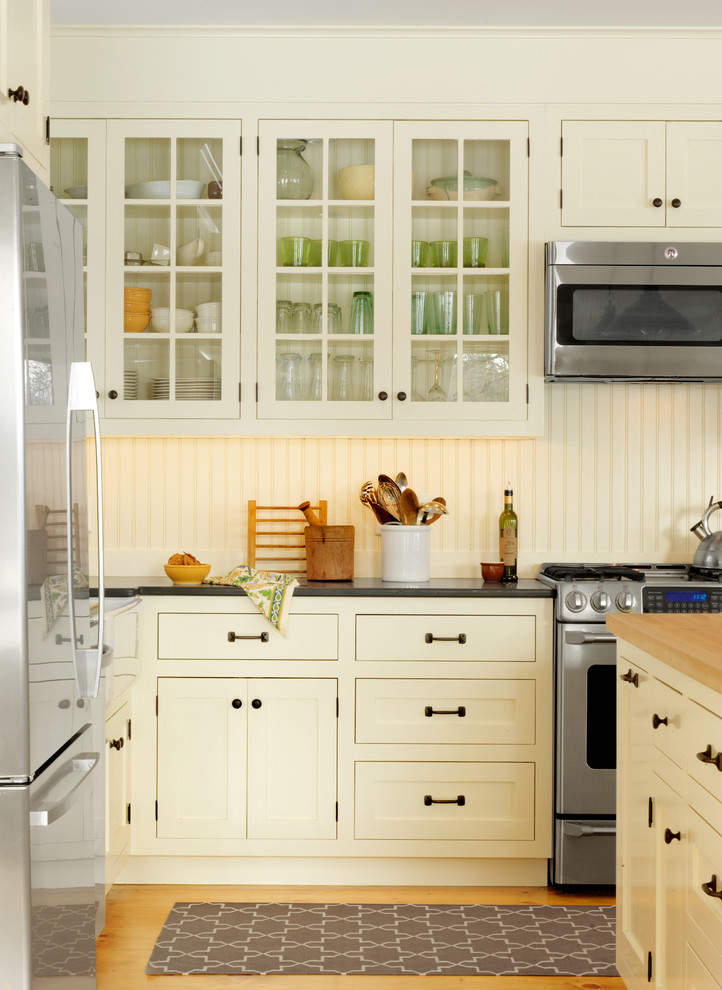 Example of a classic kitchen design in Burlington with glass-front cabinets, yellow cabinets, wood countertops and stainless steel appliances