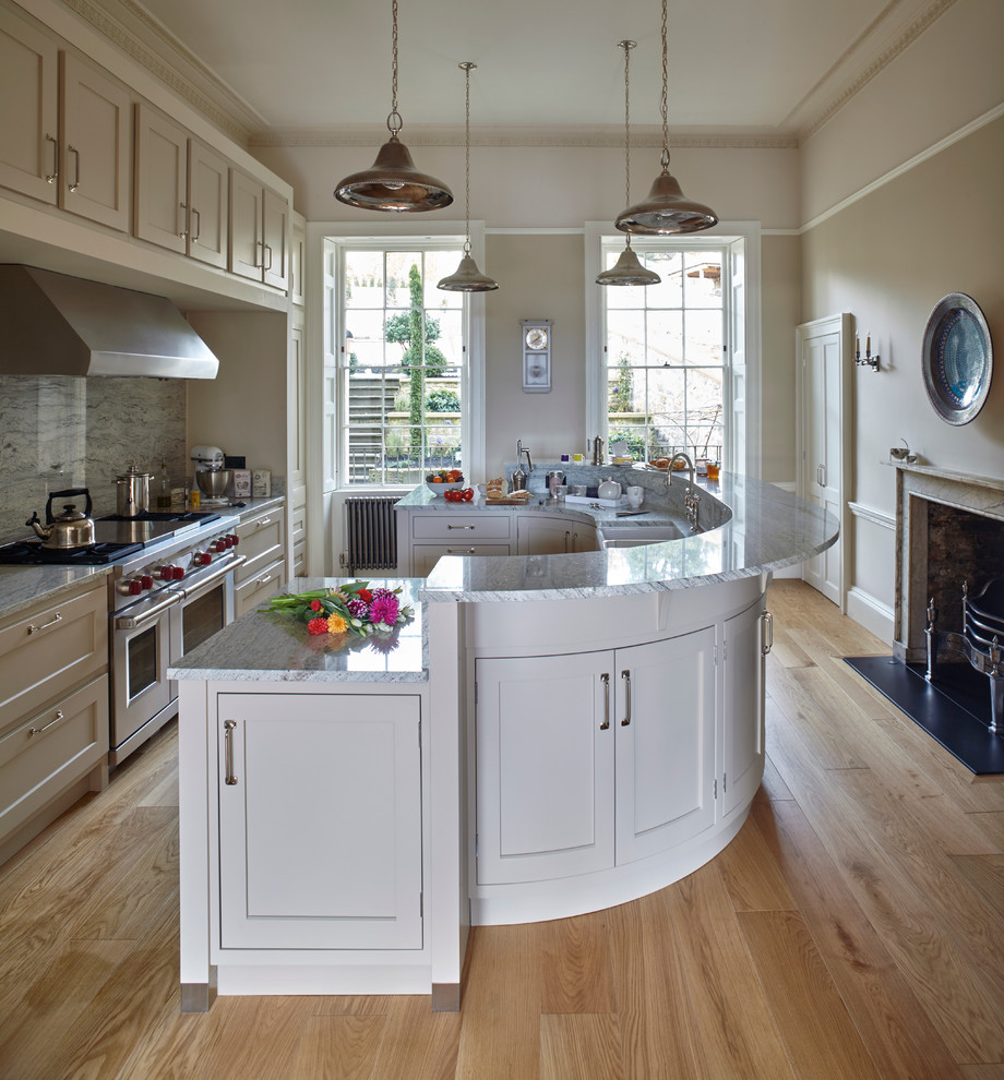 Inspiration for a large timeless galley light wood floor eat-in kitchen remodel in Wiltshire with shaker cabinets, gray cabinets, granite countertops, stainless steel appliances, an island, gray backsplash, a farmhouse sink and porcelain backsplash