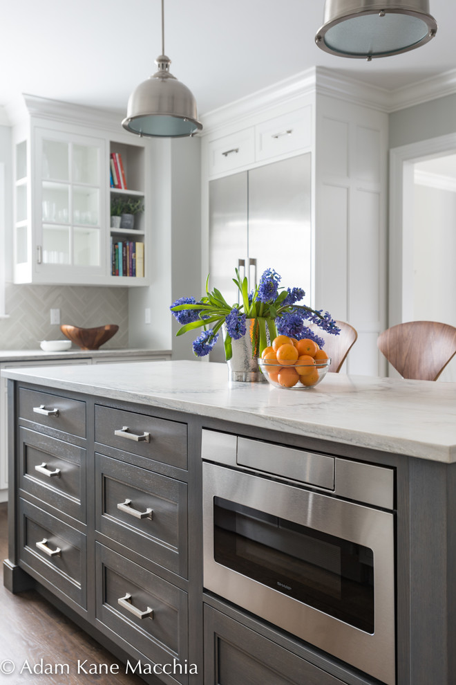 Inspiration for a mid-sized transitional l-shaped dark wood floor open concept kitchen remodel in New York with an undermount sink, shaker cabinets, white cabinets, quartzite countertops, gray backsplash, ceramic backsplash, stainless steel appliances and an island
