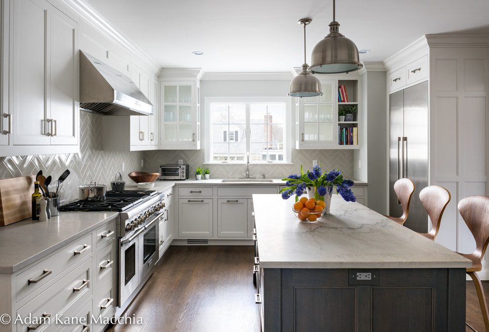 Open concept kitchen - mid-sized transitional l-shaped dark wood floor open concept kitchen idea in New York with an undermount sink, shaker cabinets, white cabinets, quartzite countertops, gray backsplash, ceramic backsplash, stainless steel appliances and an island