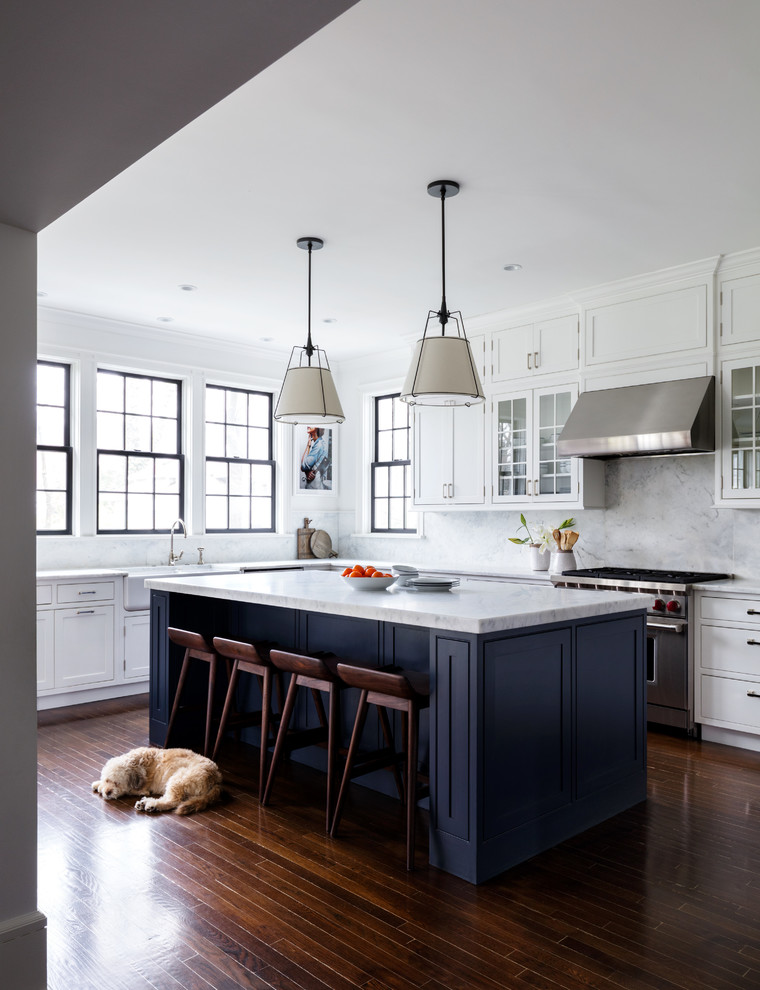 Enclosed kitchen - transitional u-shaped dark wood floor and brown floor enclosed kitchen idea in New York with a farmhouse sink, shaker cabinets, blue cabinets, gray backsplash, marble backsplash, stainless steel appliances, an island and gray countertops