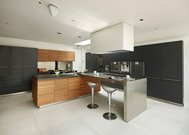 example of a trendy kitchen design in cheshire with flat panel cabinets medium tone