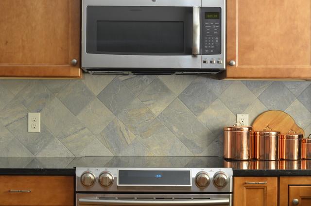 large slate tile backsplash behind lightly stained cabinets