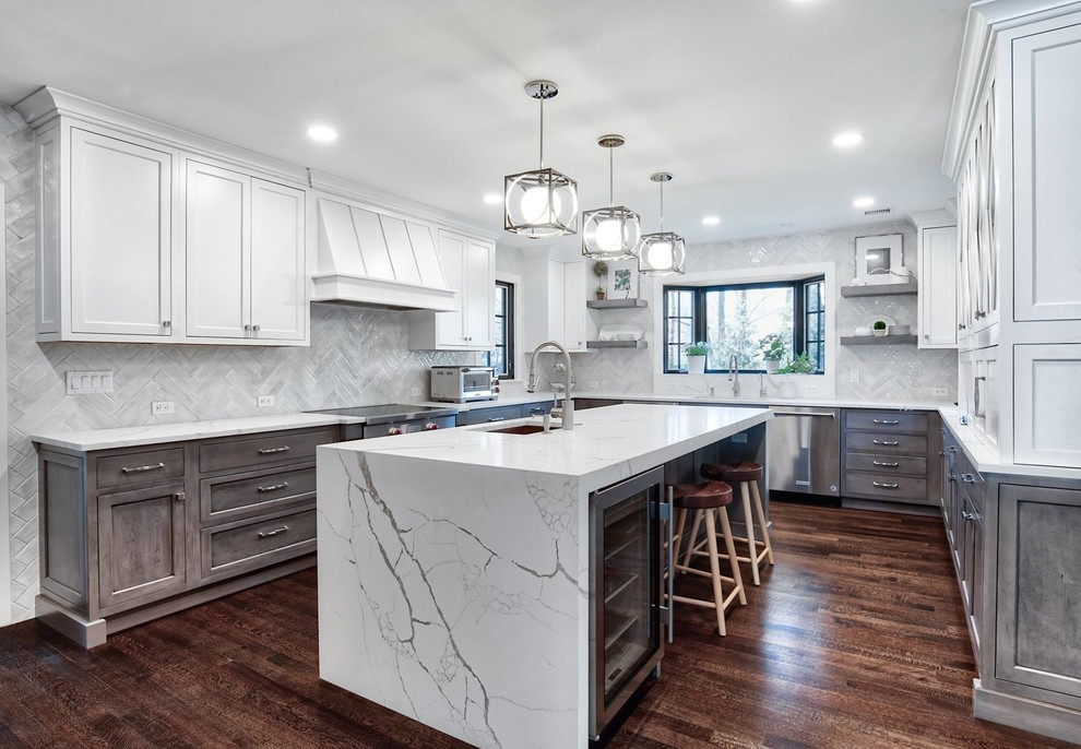 Inspiration for a large transitional u-shaped brown floor and dark wood floor kitchen remodel in New York with an undermount sink, ceramic backsplash, stainless steel appliances, an island, white countertops, shaker cabinets, white cabinets and gray backsplash