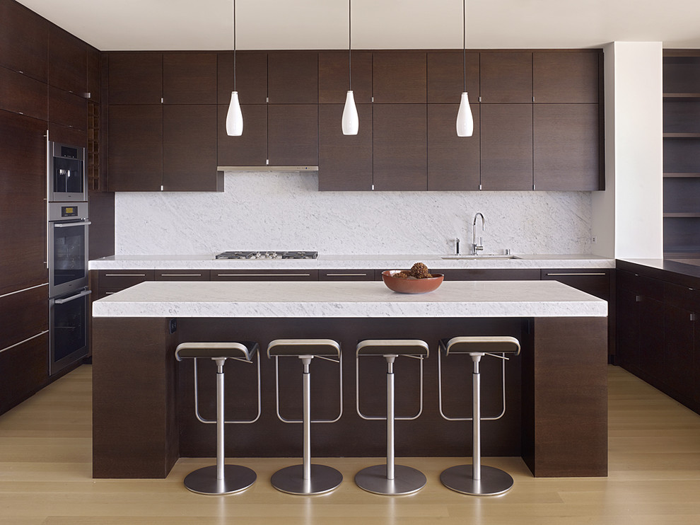 Minimalist kitchen photo in San Francisco with stainless steel appliances, flat-panel cabinets, dark wood cabinets, white backsplash, stone slab backsplash and an undermount sink