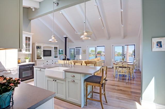 Mid-sized coastal l-shaped light wood floor open concept kitchen photo in San Francisco with a farmhouse sink, shaker cabinets, white cabinets, quartz countertops, blue backsplash, subway tile backsplash, paneled appliances and an island