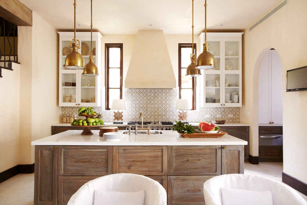Example of a tuscan eat-in kitchen design in Other with an undermount sink, glass-front cabinets, white cabinets, multicolored backsplash, stainless steel appliances and an island