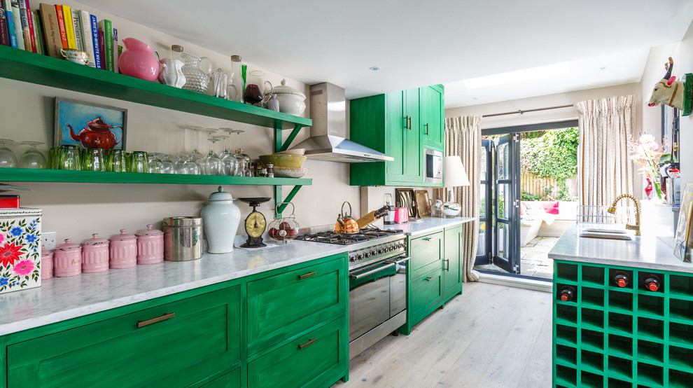 Example of an eclectic galley light wood floor and beige floor kitchen design in New York with an undermount sink, green cabinets, stainless steel appliances, no island and recessed-panel cabinets