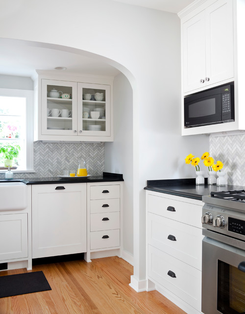 Inspiration for a large timeless u-shaped light wood floor eat-in kitchen remodel in Seattle with a farmhouse sink, recessed-panel cabinets, white cabinets, granite countertops, gray backsplash, glass tile backsplash, stainless steel appliances and no island