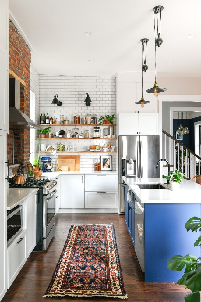 Mid-sized transitional l-shaped dark wood floor and brown floor eat-in kitchen photo in Other with an undermount sink, shaker cabinets, blue cabinets, quartz countertops, white backsplash, subway tile backsplash, stainless steel appliances, an island and white countertops