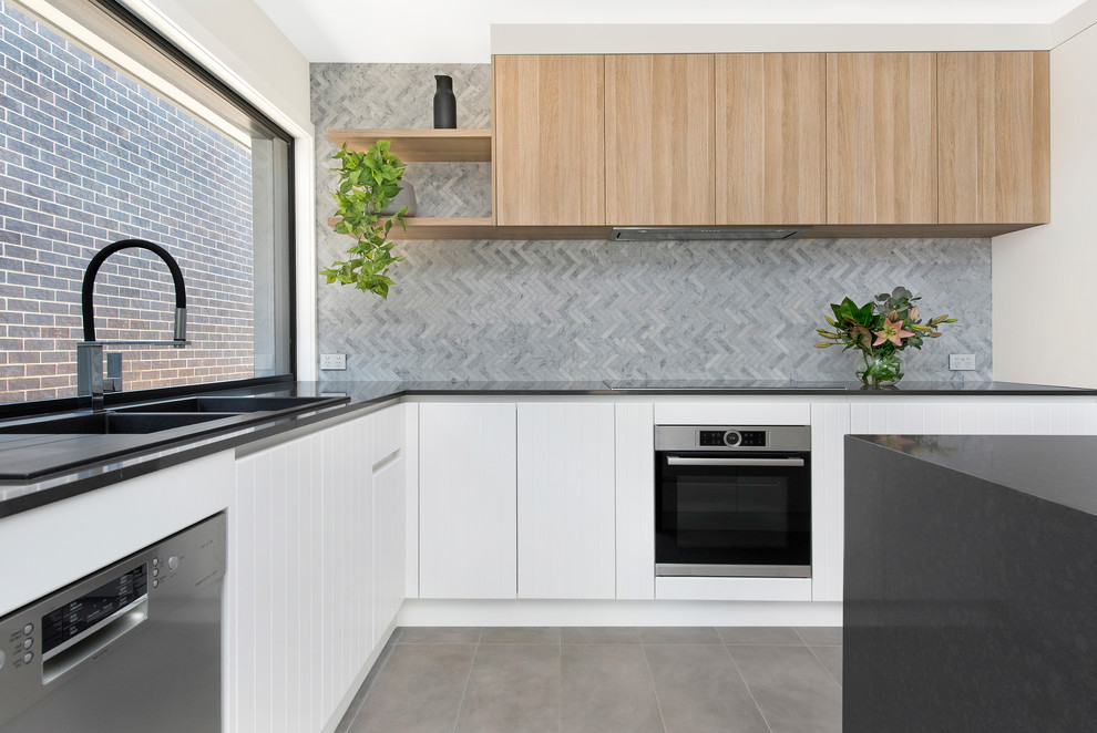 Example of a trendy l-shaped gray floor kitchen design in Canberra - Queanbeyan with a drop-in sink, flat-panel cabinets, white cabinets, gray backsplash, stainless steel appliances, an island and gray countertops
