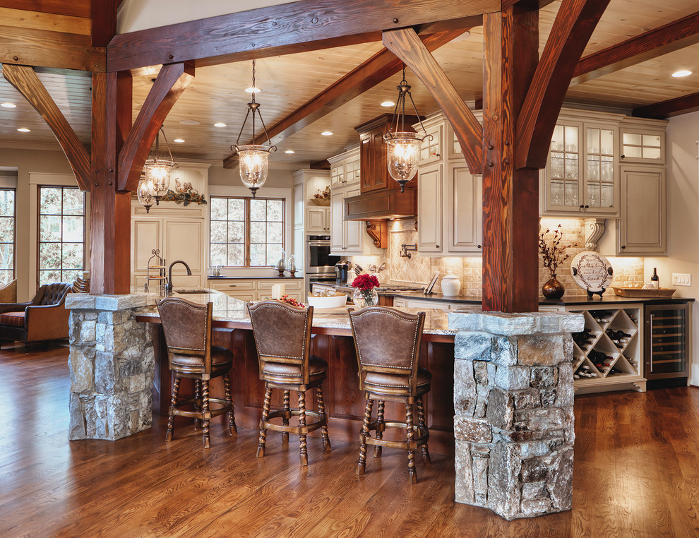 Inspiration for a rustic l-shaped medium tone wood floor and brown floor eat-in kitchen remodel in Other with an undermount sink, raised-panel cabinets, gray cabinets, beige backsplash, paneled appliances, an island and gray countertops