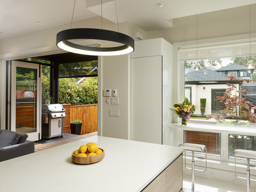 Kitchen - contemporary u-shaped ceramic tile kitchen idea in Vancouver with an undermount sink, flat-panel cabinets, quartz countertops, white backsplash, glass tile backsplash, paneled appliances and an island
