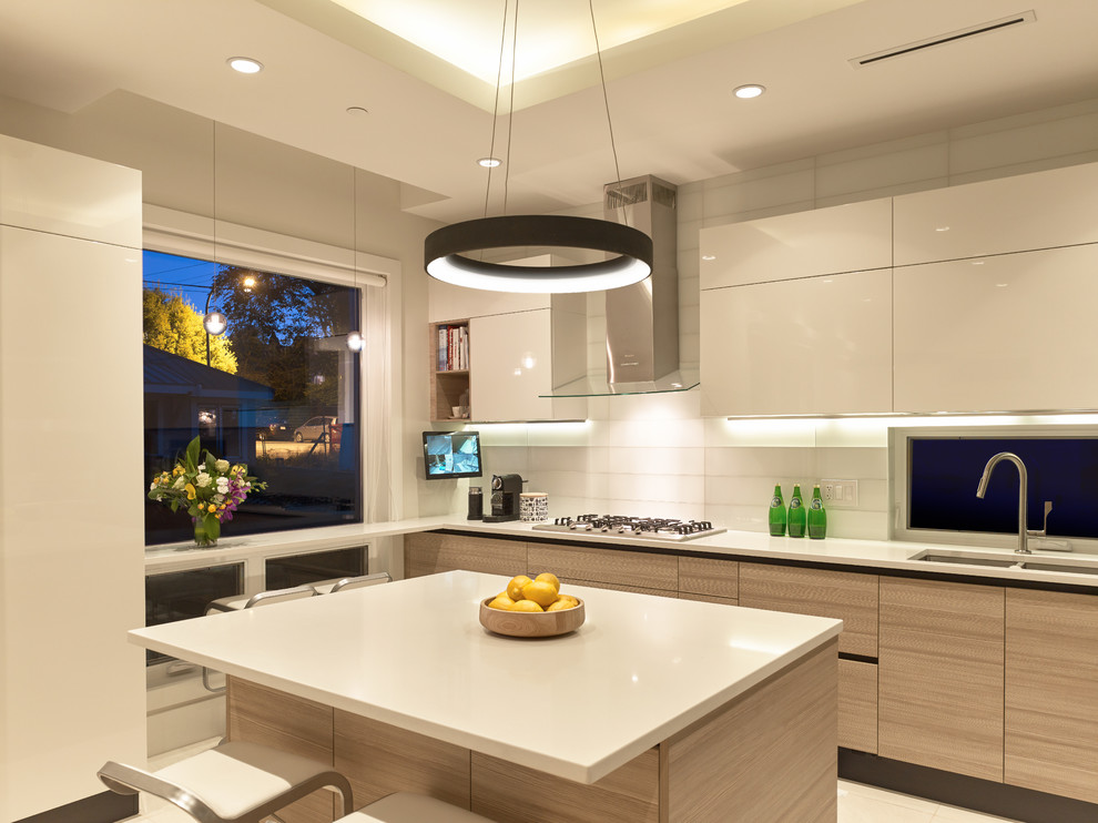 Inspiration for a contemporary u-shaped ceramic tile kitchen remodel in Vancouver with an undermount sink, flat-panel cabinets, quartz countertops, white backsplash, glass tile backsplash, paneled appliances and an island