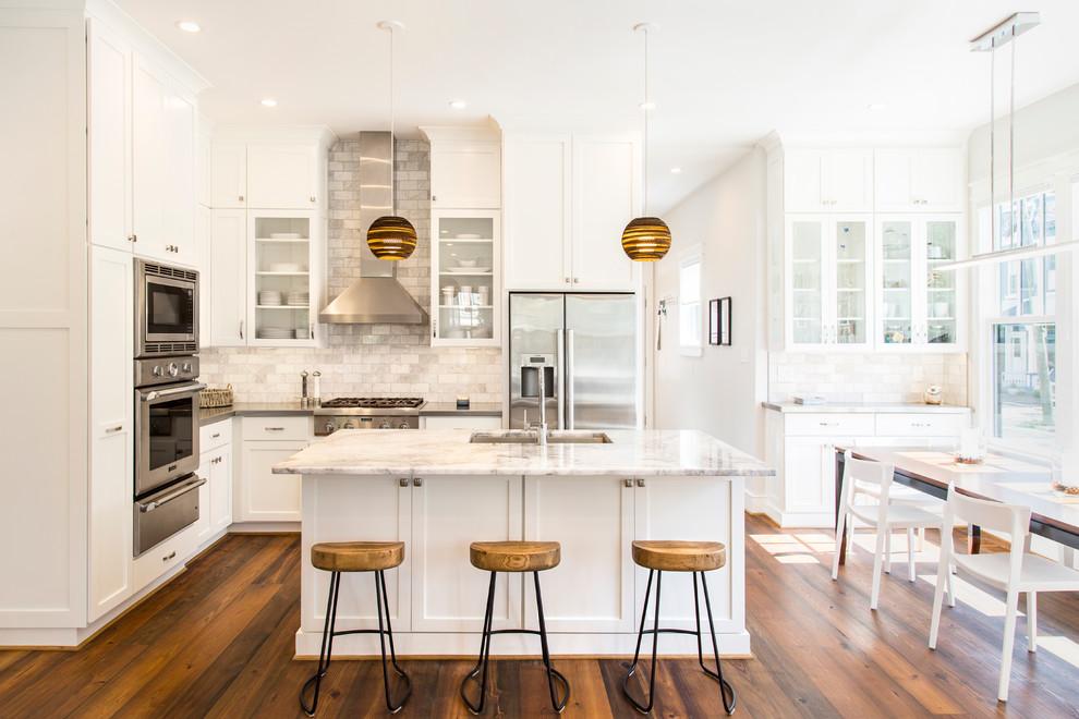 Immagine di una cucina chic con lavello sottopiano, ante in stile shaker, ante bianche, paraspruzzi grigio, elettrodomestici in acciaio inossidabile, parquet scuro e isola