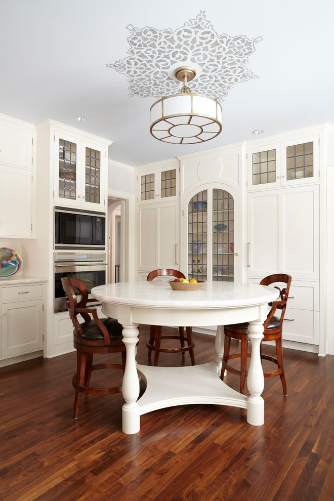Eat-in kitchen - traditional eat-in kitchen idea in Minneapolis with shaker cabinets, white cabinets and paneled appliances