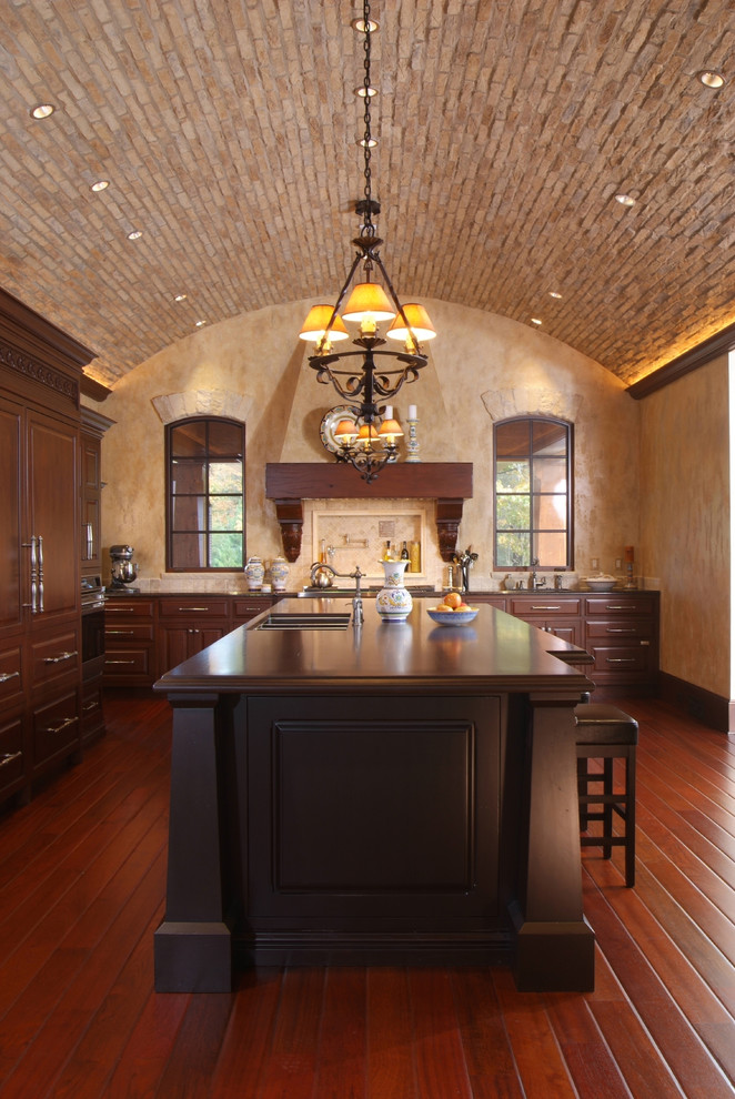 Inspiration for a mediterranean dark wood floor kitchen remodel in Grand Rapids with raised-panel cabinets, dark wood cabinets, paneled appliances and an undermount sink