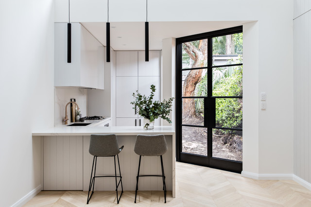 This is an example of a contemporary l-shaped kitchen in Sydney with an undermount sink, flat-panel cabinets, grey cabinets, white splashback, marble splashback, light hardwood floors, a peninsula, beige floor and white benchtop.