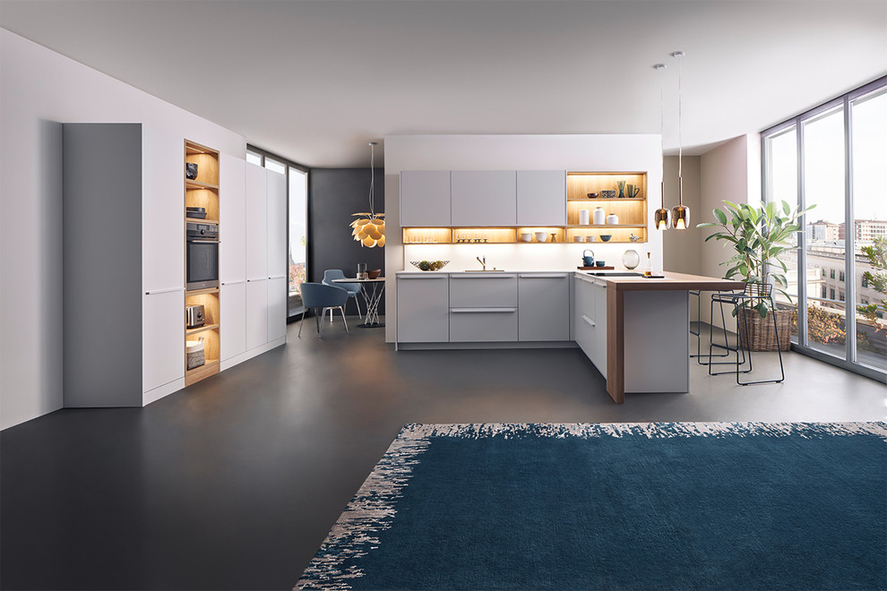 Example of a mid-sized minimalist l-shaped kitchen design in New York with flat-panel cabinets, white cabinets, wood countertops and a peninsula