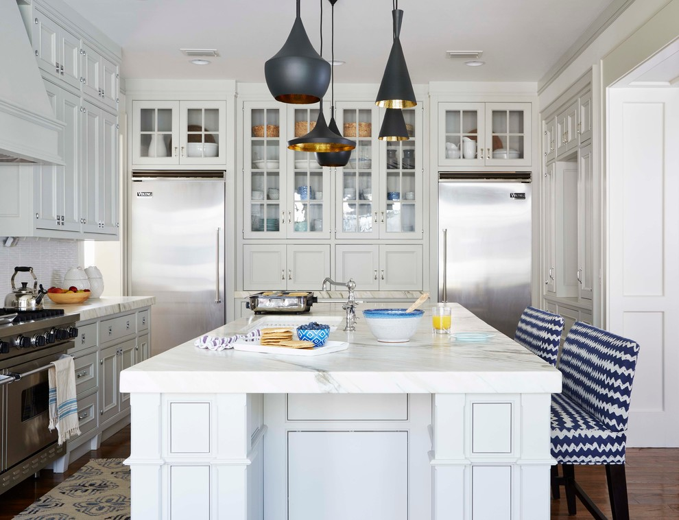 Example of a beach style kitchen design in Jacksonville with white cabinets and an island