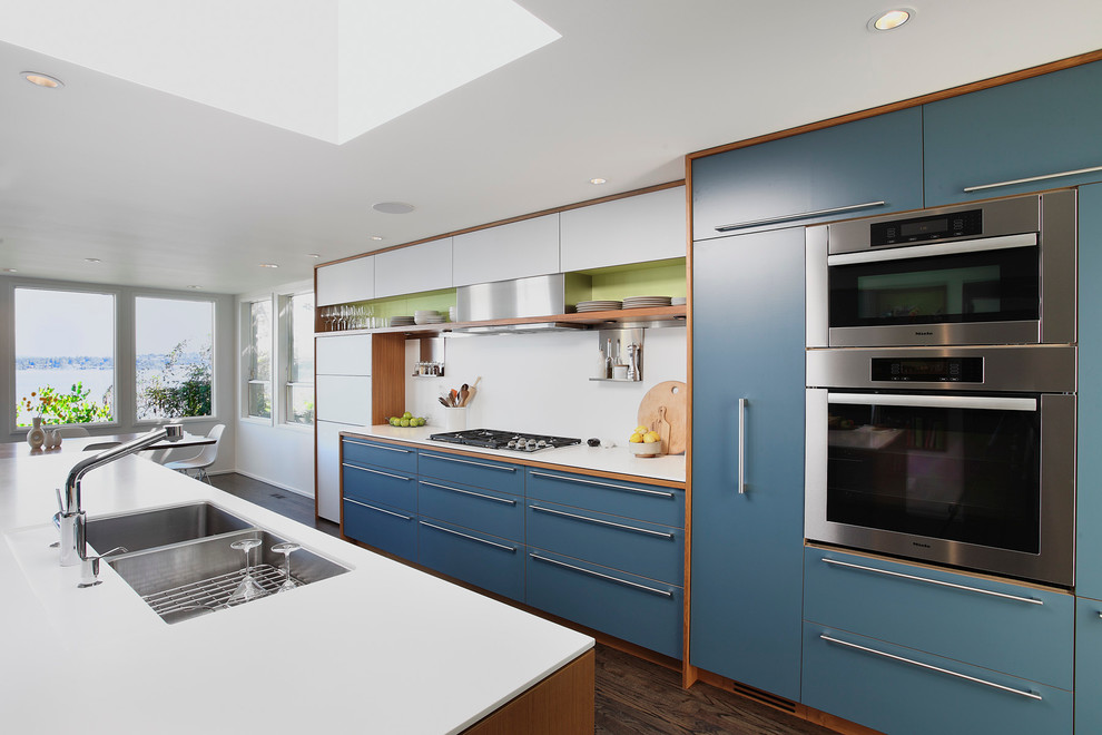 Large trendy galley dark wood floor and brown floor eat-in kitchen photo in Seattle with flat-panel cabinets, stainless steel appliances, a double-bowl sink, blue cabinets, white backsplash and an island