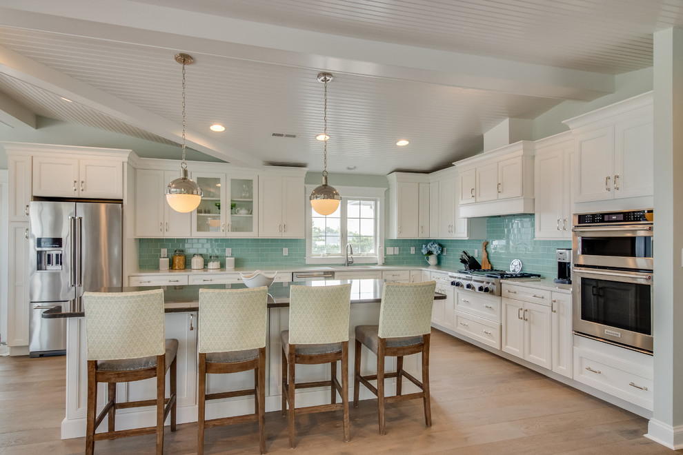 Kitchen - coastal l-shaped medium tone wood floor and brown floor kitchen idea in Other with shaker cabinets, white cabinets, blue backsplash, subway tile backsplash, stainless steel appliances and an island