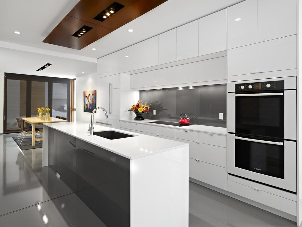 Foto di una cucina design con lavello a vasca singola, ante lisce, ante bianche, paraspruzzi grigio, paraspruzzi con lastra di vetro, elettrodomestici da incasso e top bianco