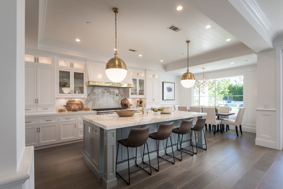 Inspiration for a large timeless galley brown floor and dark wood floor eat-in kitchen remodel in Los Angeles with a farmhouse sink, shaker cabinets, white backsplash, stainless steel appliances, an island and white cabinets
