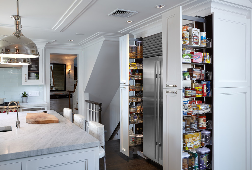 Large transitional l-shaped dark wood floor kitchen pantry photo in New York with an undermount sink, glass-front cabinets, white cabinets, marble countertops, white backsplash, glass tile backsplash, stainless steel appliances and an island