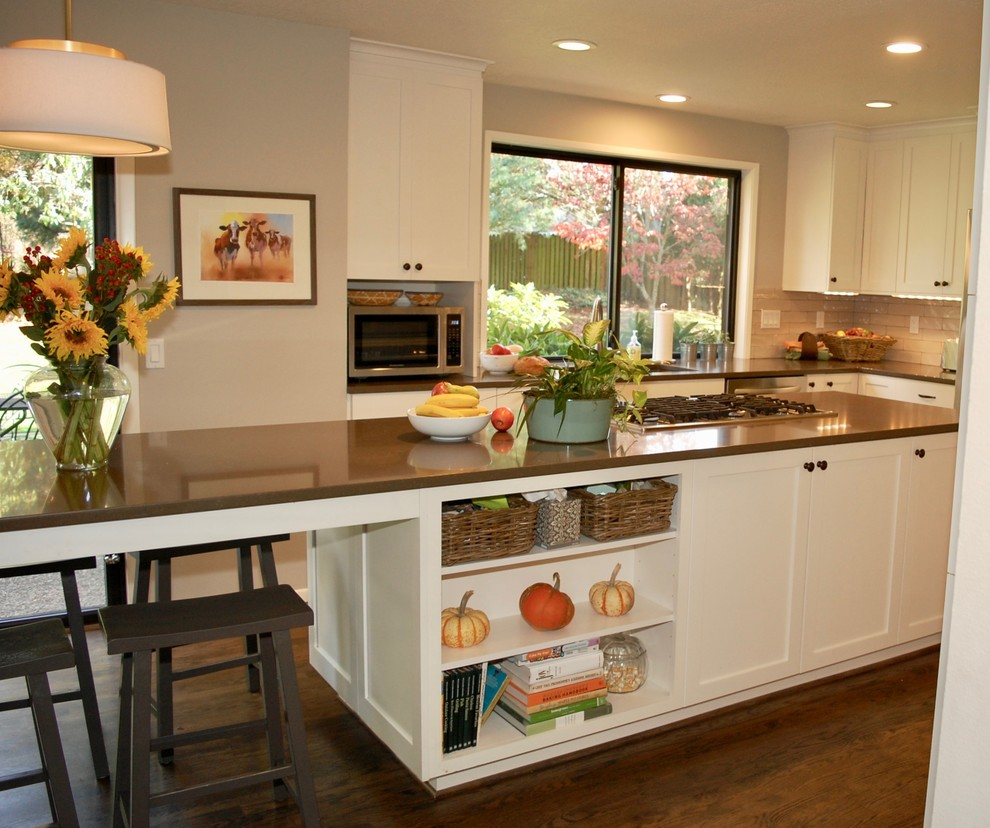 Mid-sized elegant l-shaped medium tone wood floor open concept kitchen photo in Portland with an undermount sink, shaker cabinets, white cabinets, quartz countertops, beige backsplash, subway tile backsplash, stainless steel appliances, an island and brown countertops