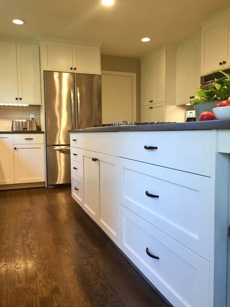 Inspiration for a mid-sized timeless l-shaped medium tone wood floor open concept kitchen remodel in Portland with an undermount sink, shaker cabinets, white cabinets, quartz countertops, beige backsplash, subway tile backsplash, stainless steel appliances, an island and brown countertops