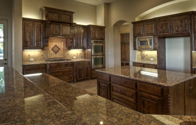 Lights above cabinets and pretty tile work around backsplash
