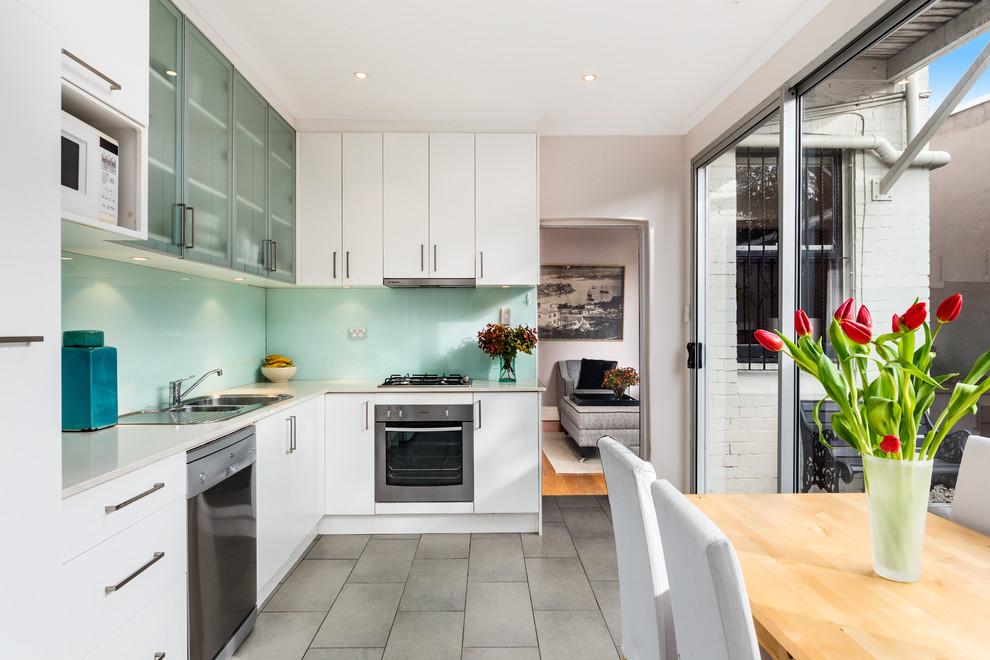 Foto di una cucina design con lavello a doppia vasca, ante lisce, ante bianche, elettrodomestici in acciaio inossidabile e nessuna isola