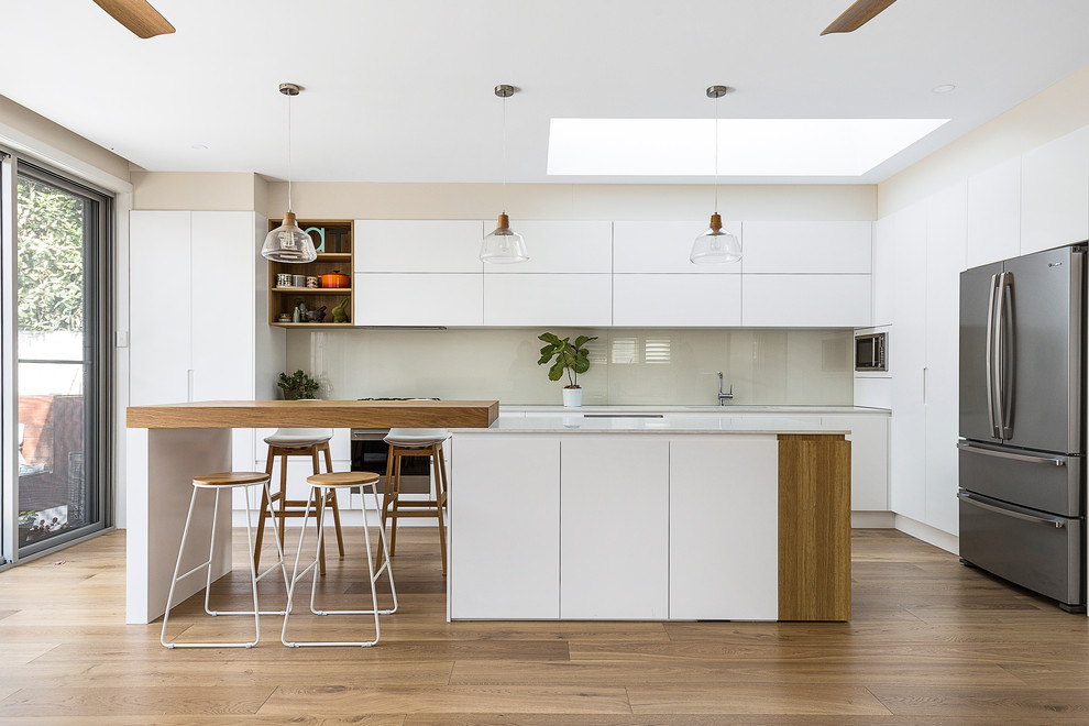 Design ideas for a large modern l-shaped open plan kitchen in Sydney with an undermount sink, flat-panel cabinets, white cabinets, glass sheet splashback, stainless steel appliances, medium hardwood floors, an island, quartz benchtops, white splashback, white benchtop and brown floor.
