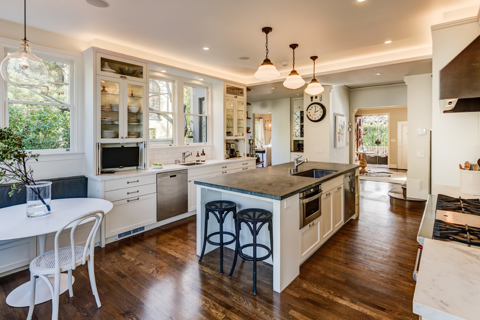 Transitional galley dark wood floor and brown floor eat-in kitchen photo in San Francisco with an undermount sink, shaker cabinets, white cabinets, white backsplash, subway tile backsplash, stainless steel appliances, an island and gray countertops