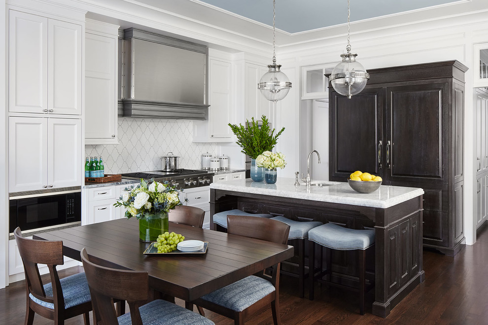 Eat-in kitchen - mid-sized traditional u-shaped dark wood floor and brown floor eat-in kitchen idea in Chicago with an undermount sink, raised-panel cabinets, black cabinets, marble countertops, white backsplash, ceramic backsplash, paneled appliances, an island and gray countertops