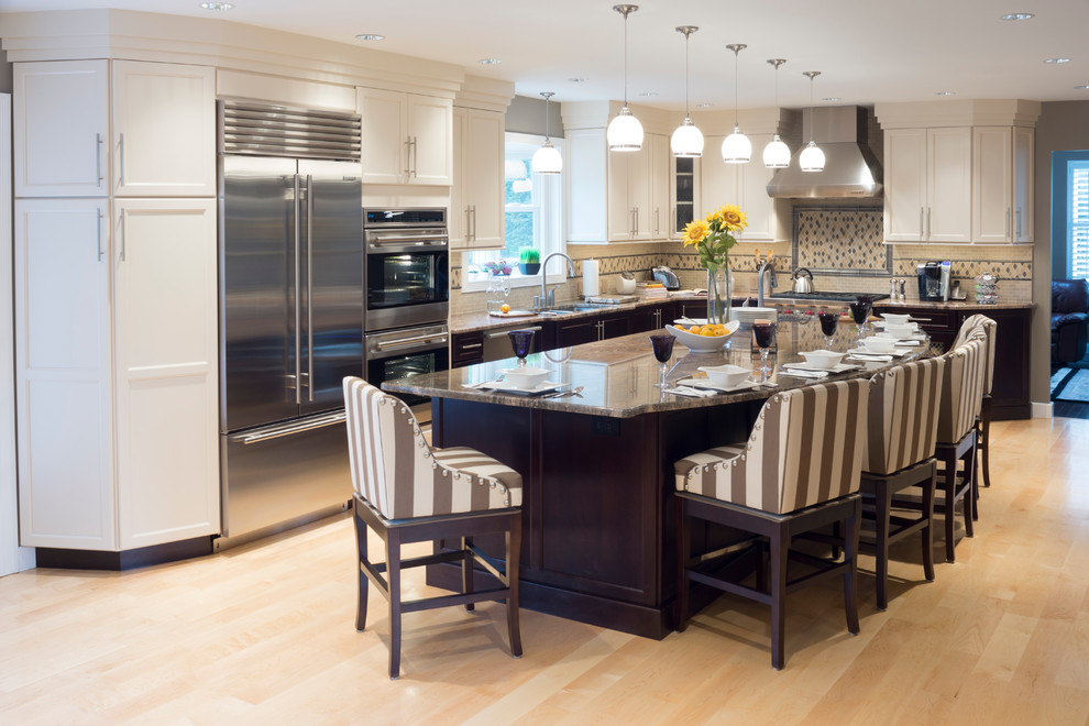 Huge elegant l-shaped light wood floor open concept kitchen photo in Providence with stainless steel appliances, granite countertops, an island, shaker cabinets, white cabinets, beige backsplash, stone tile backsplash and an undermount sink