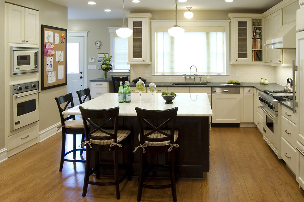 Kitchen - traditional l-shaped kitchen idea in Chicago with glass-front cabinets, white appliances, white cabinets, soapstone countertops and white backsplash