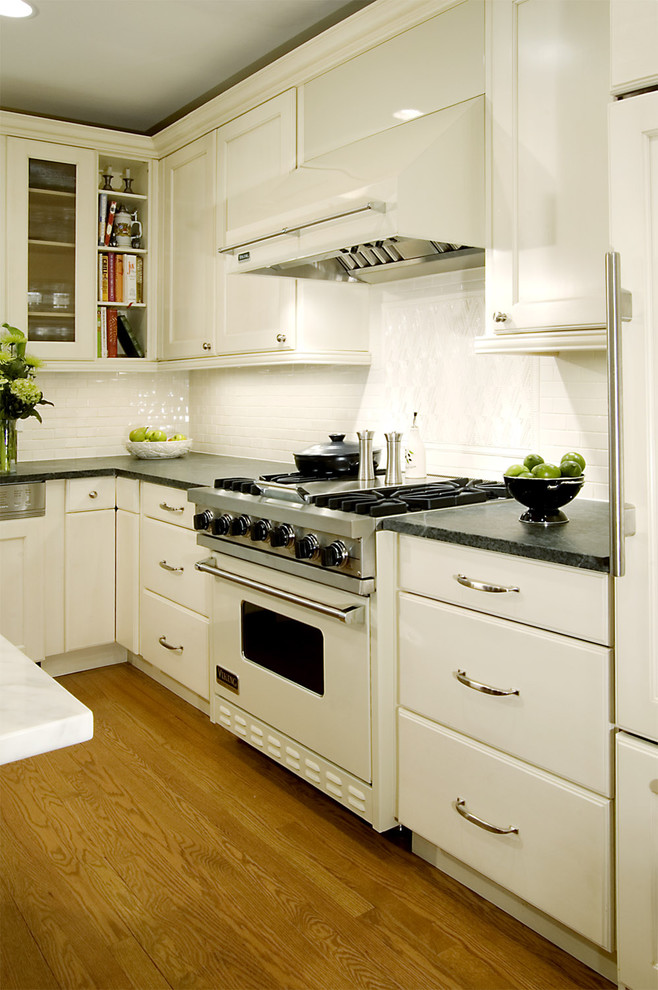 Example of a classic kitchen design in Chicago with white appliances, white cabinets, white backsplash and soapstone countertops