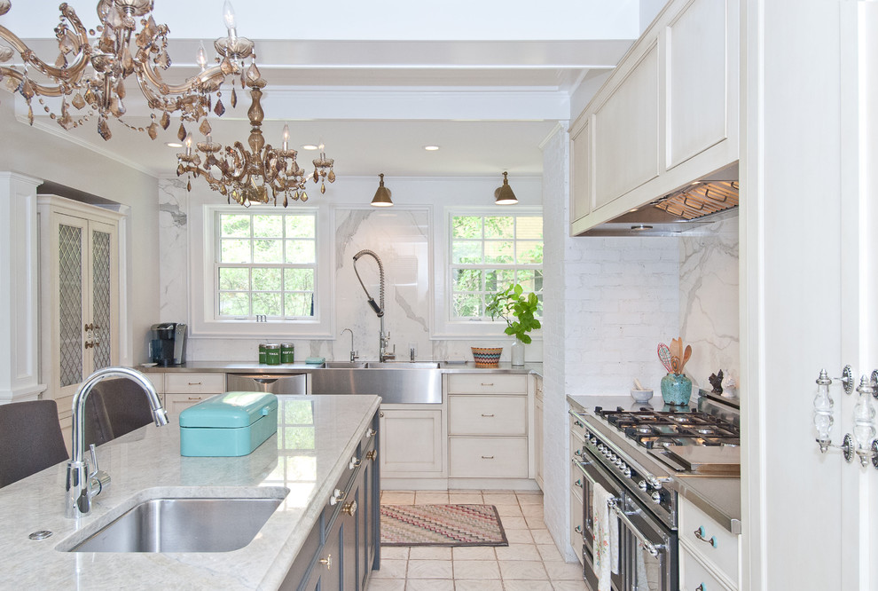 Example of a classic kitchen design in Chicago with stainless steel countertops, an undermount sink, recessed-panel cabinets, white backsplash, stainless steel appliances and marble backsplash