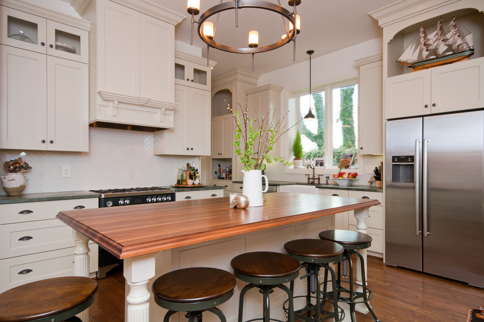 Inspiration for a timeless kitchen remodel in Nashville with a farmhouse sink, shaker cabinets, beige cabinets, white backsplash and stainless steel appliances
