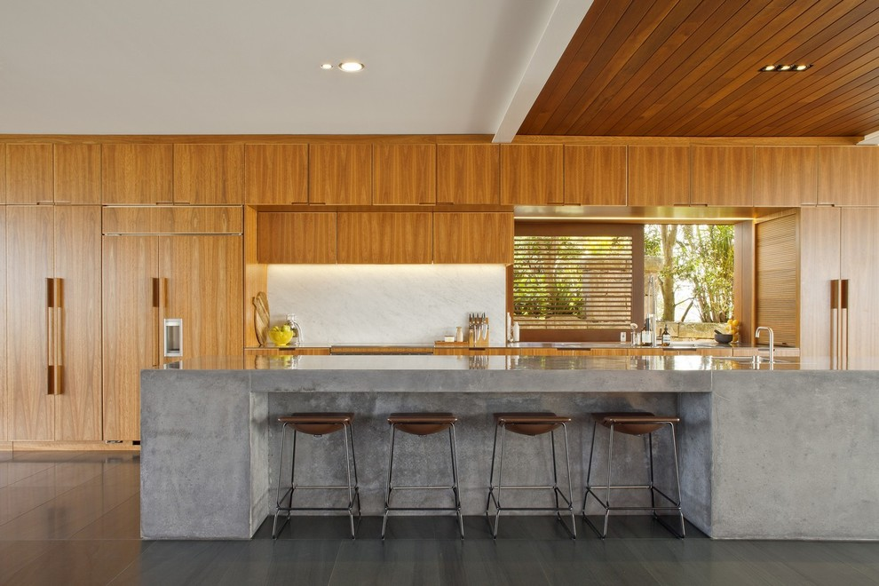 Inspiration for a large contemporary galley slate floor eat-in kitchen remodel in Sydney with an undermount sink, medium tone wood cabinets, concrete countertops, gray backsplash, stone slab backsplash, stainless steel appliances and an island
