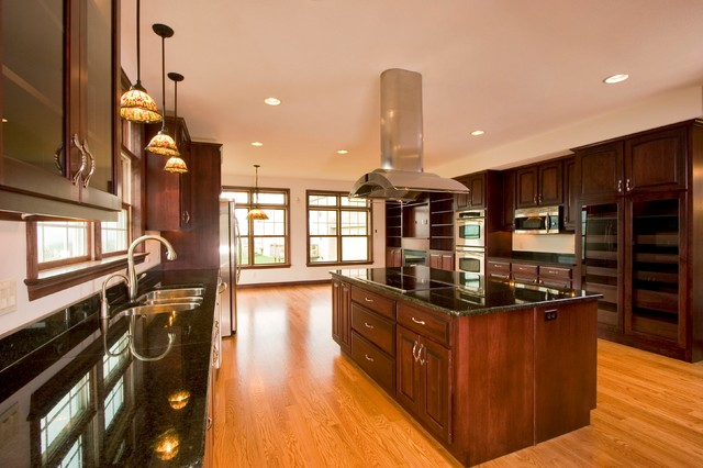 Large transitional u-shaped medium tone wood floor eat-in kitchen photo in Other with a double-bowl sink, shaker cabinets, dark wood cabinets, granite countertops, stainless steel appliances and an island
