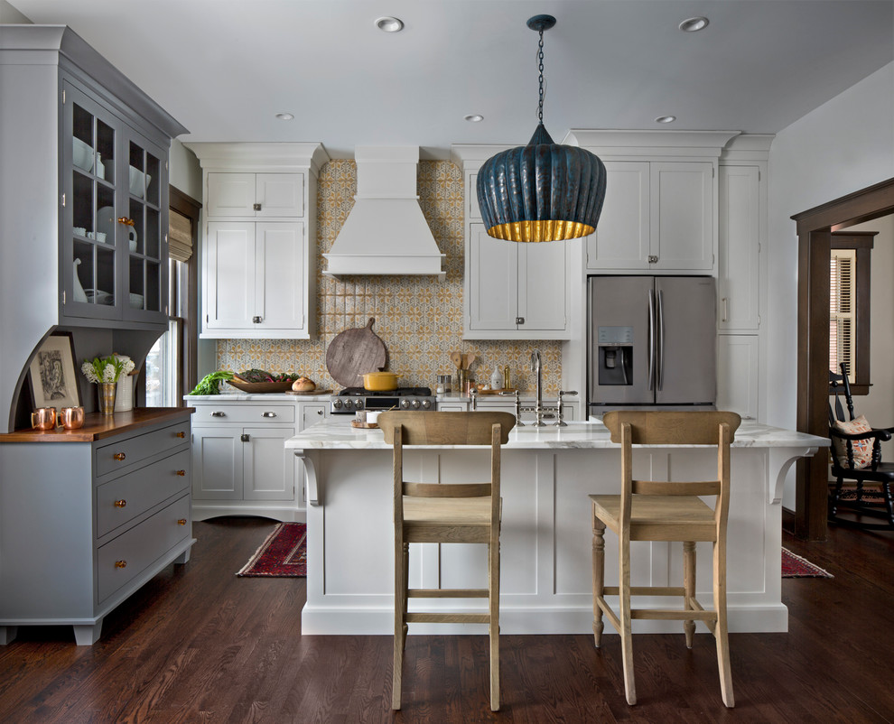 Transitional dark wood floor kitchen photo in Detroit with shaker cabinets, white cabinets, multicolored backsplash, stainless steel appliances and an island