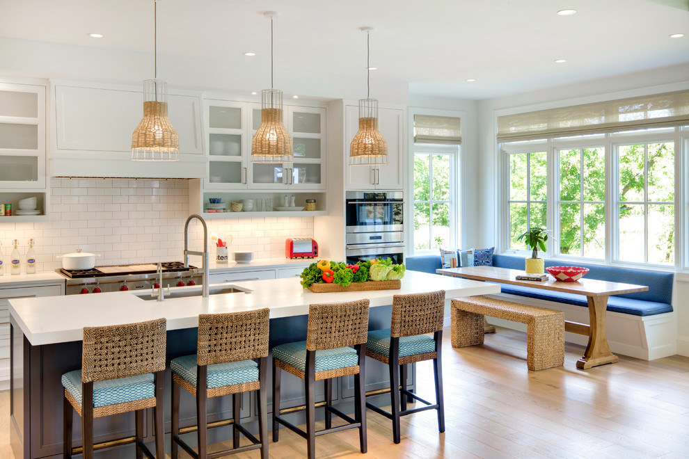 Beach style light wood floor eat-in kitchen photo in Minneapolis with an undermount sink, shaker cabinets, white cabinets, white backsplash, subway tile backsplash and an island